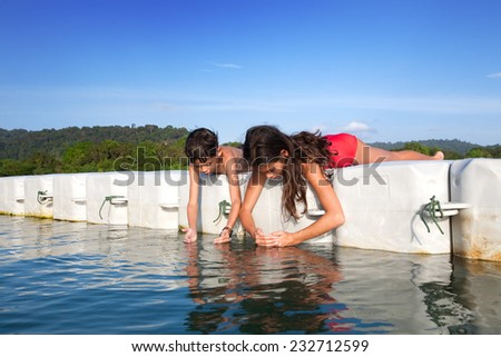 Young boy and  his sister catching tiny prawns while they were on floating platform on tropical island - stock photo