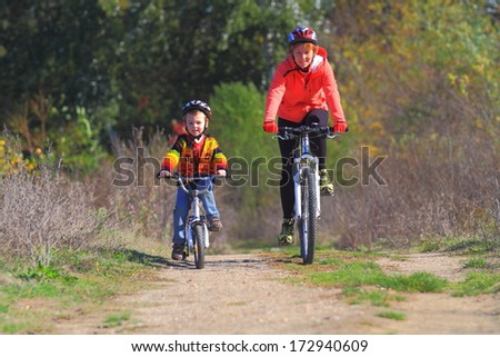 Young boy and mother during bike ride in autumn road - stock photo