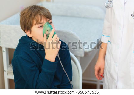 Young boy and nurse making inhalation with nebuliser in exam room - stock photo