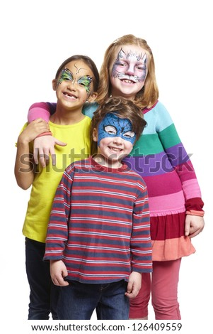 Young boy and two girls with face painting of cat, butterfly and superhero smiling on white background