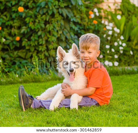 young boy and White Swiss Shepherd`s puppy - stock photo