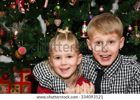 Young boy and young girl happy and looking at camera on christmas day