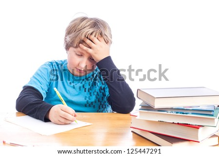 Young boy at a desk hand on his head frustrated doing homework. isolated on white with paper, books and desk. Space for your text. - stock photo