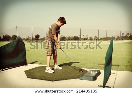 Young boy at golf driving range with a retro instagram look. - stock photo