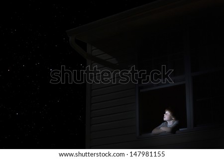 Young boy at open window looking at night sky - stock photo