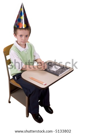 Young boy at school desk with a party hat on his head with book and pencils isolated over a white background