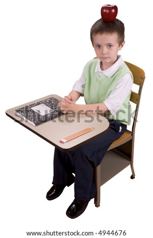 Young boy at school desk with an apple on his head with book and pencils isolated over a white background