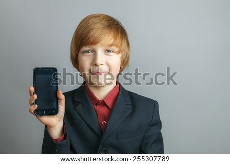 Young boy at the phone, isolated over gray - stock photo