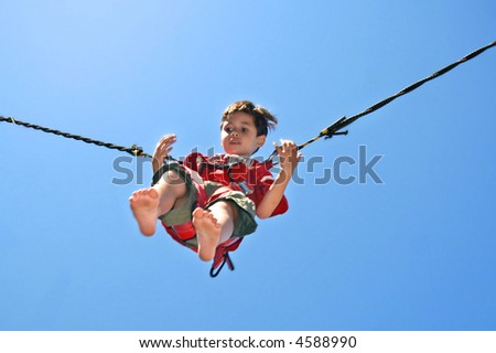 Young boy attached to jumping rope on trampoline. - stock photo