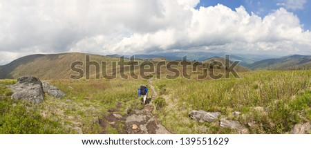 young boy backpacking over mountain, wide panorama - stock photo