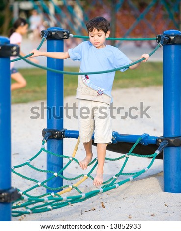 Young boy balancing on rope activity in playground - stock photo