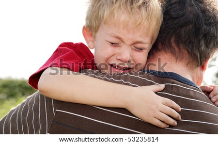 Young boy being comforted by his father - stock photo
