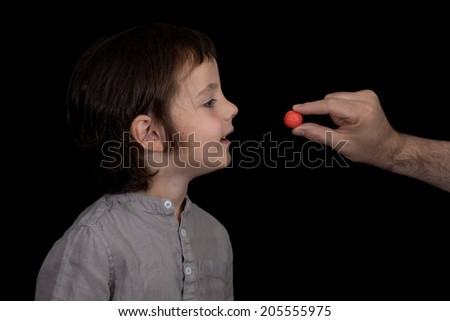 Young boy being tempted by candy. Black background. - stock photo