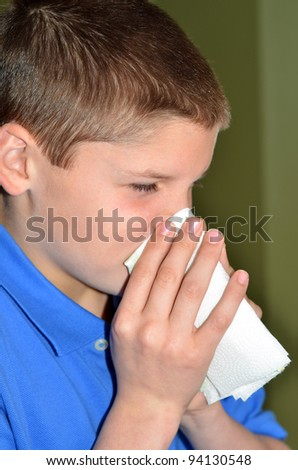 Young boy blowing his nose very hard
