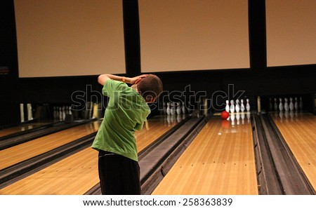 young boy bowling and hoping for a spare - stock photo
