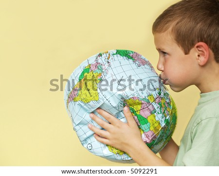 young boy breathing life back into a deflating planet earth - stock photo