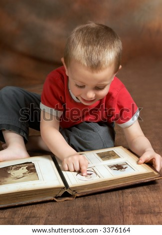 Young boy browsing an antique family album (the faces on the photos in the album cannot be recognized) - stock photo