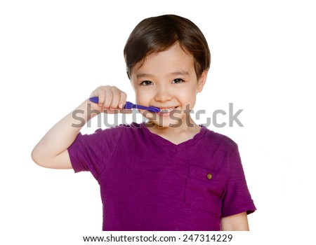Young boy brushing teeth, isolated on white. Young child brushing teeth. Purple tooth brush. Dental smile. Kid happy to brush his teeth for his daily routine. - stock photo