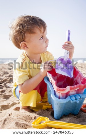 Young boy building sand castles at the beach - stock photo