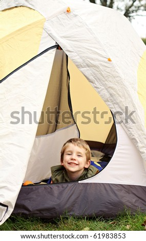 Young boy camping in tent - stock photo