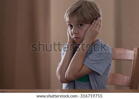 Young boy cannot hear any more his parents arguing - stock photo
