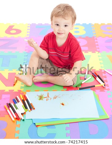 Young boy child drawing on kids alphabet mat. Isolated on white.