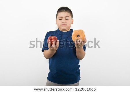 Young boy choosing between an apple and donut isolated over white background - stock photo