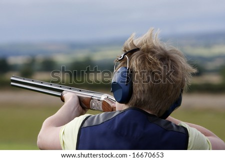 Young boy clay pigeon shooting - stock photo