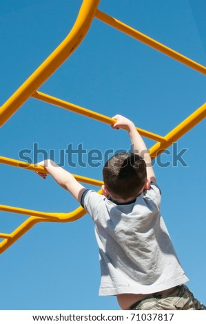 young boy climbing on monkey bars - stock photo