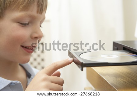 Young Boy Closing DVD Player With Finger - stock photo