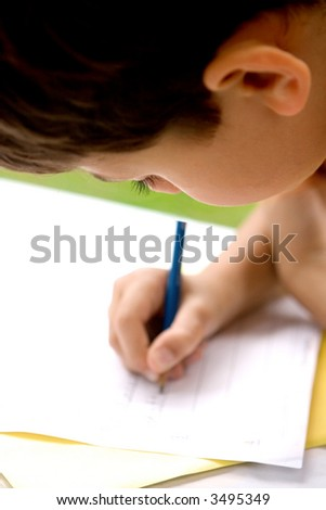 Young boy concentrating on his writing homework from school, enjoying it outdoors.