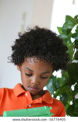 Young boy contemplates using his toy watergun. - stock photo