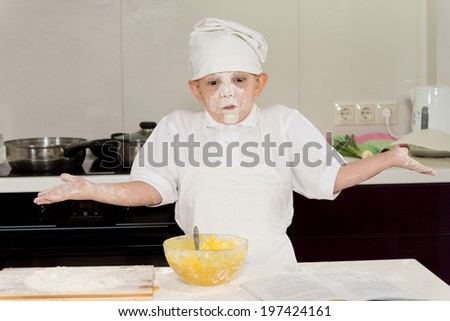 Young boy cook with a face full of flour shrugging his shoulders at the mishap as he stands in his chefs uniform baking a cake - stock photo