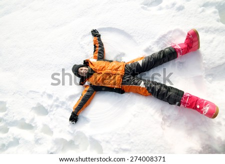 young boy creates the outline of an Angel in the snow in the mountains - stock photo