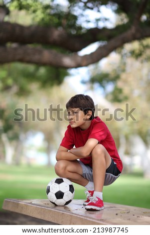 Young boy crouched on a table in the park with a soccer ball