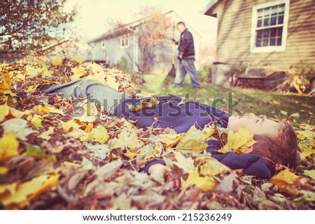 Young boy daydreaming in a pile of fall leaves while his father  - stock photo