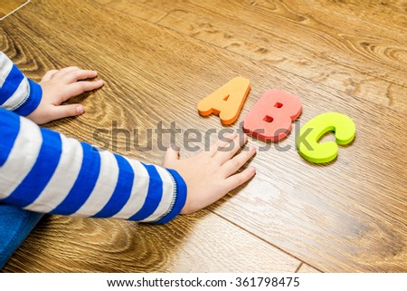 young boy demonstrating his collection of capital letters while sitting on brown wooden floor - stock photo