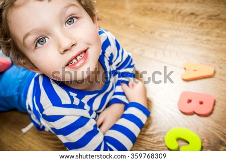young boy demonstrating his collection of capital letters with happy and smiling face while laying on brown wooden floor - stock photo