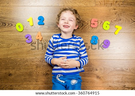 young boy demonstrating his collection of numbers with happy and smiling face while laying on brown wooden floor - stock photo