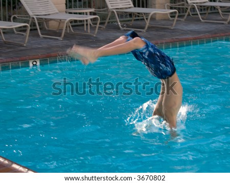 Young boy diving head first into a swimming pool with head in the water and feet still in the air