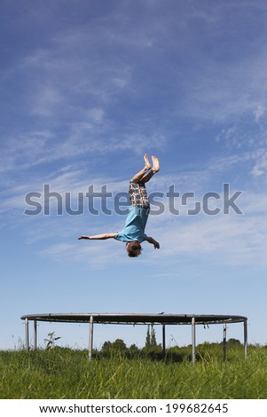 Young boy doing a backflip on a trampoline on green meadow - stock photo