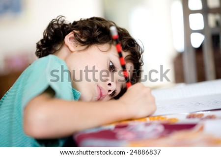Young boy doing his homework at home. - stock photo
