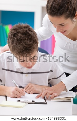 young boy doing homework with assistance of his sister
