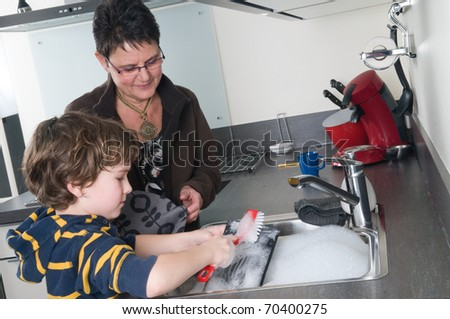Young boy doing the dishes while grandma is helping.