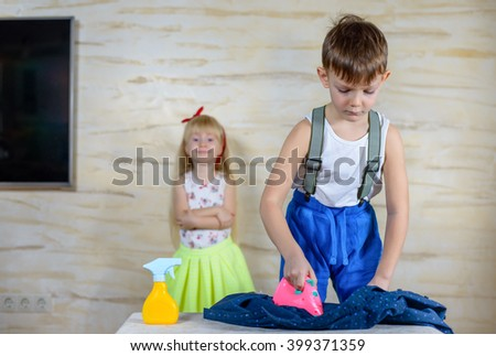 Young boy doing the ironing at home using a colorful pink plastic toy iron watched from the background with a pretty happy smiling little blond girl