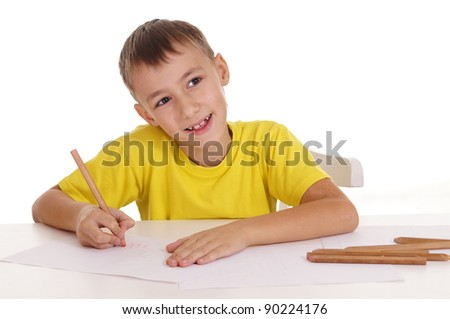 young boy drawing at table on white