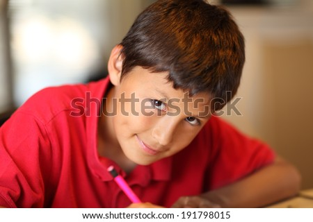 Young boy drawing for homework - with very shallow depth of field