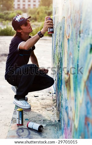 Young boy drawing graffiti on a wall with a spray can