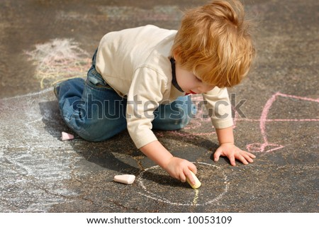 Young boy drawing outside with chalk - stock photo