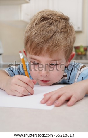 Young boy drawing with a pencil